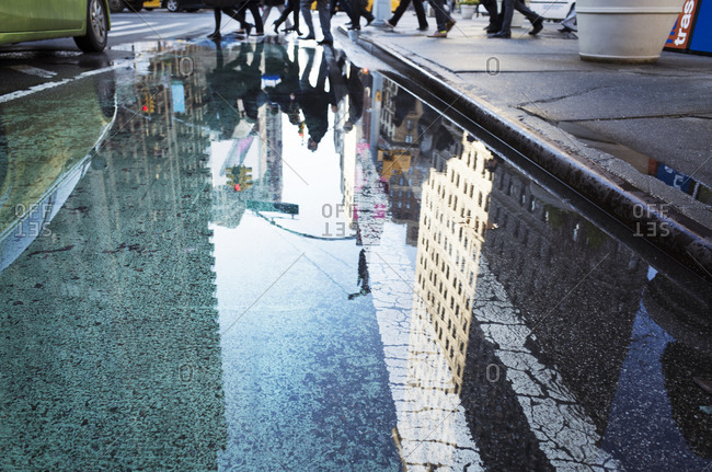 A busy city intersection reflected in a puddle