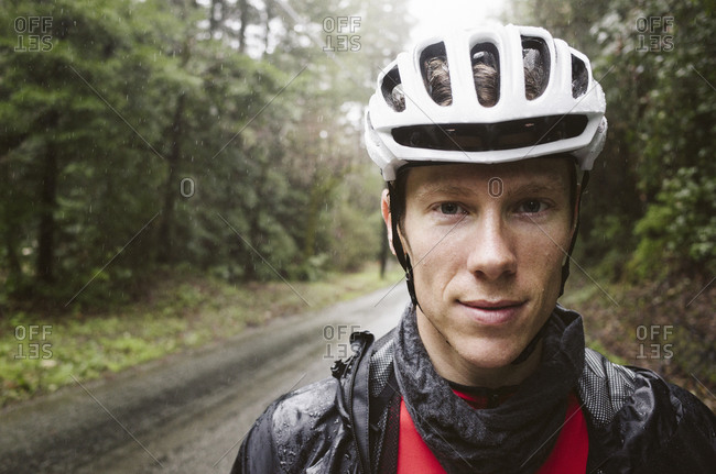 A cyclist standing in the rain