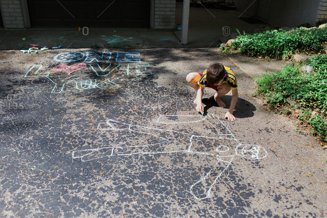 Boy drawing with chalk on home driveway