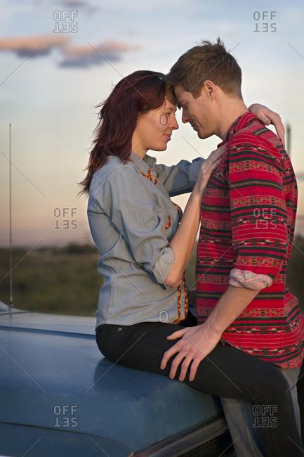 Couple embracing on hood of truck