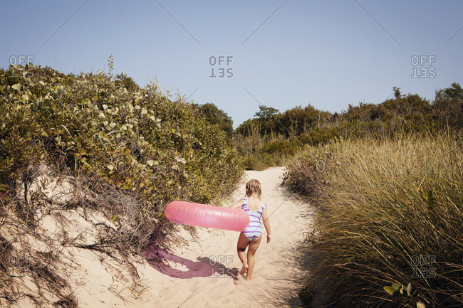 Girl walking up beach path carrying ring floatie