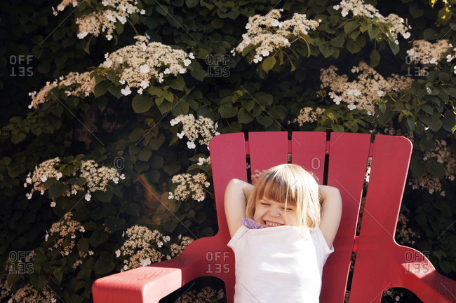 Girl lounging in Adirondack chair by hush
