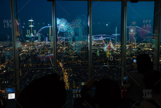 May 10, 2015: People in city overlook with light show in Japan