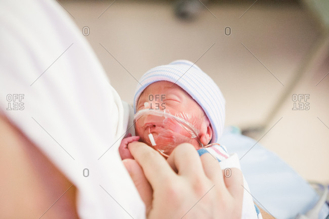 Mother holding her premature baby