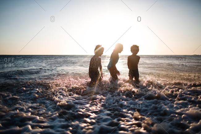 Children bathing in the ocean at sunset