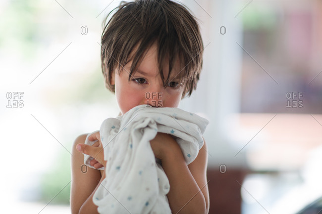 Young boy hugging a blanket