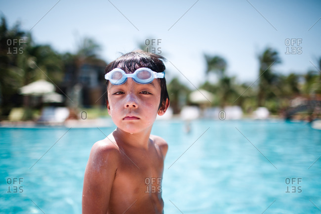 Young boy wearing swimming goggles at a pool