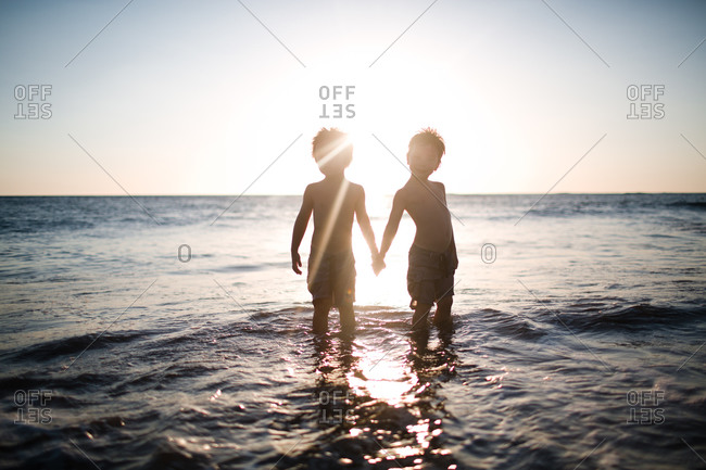 Twins holding hands on a beach at sunset