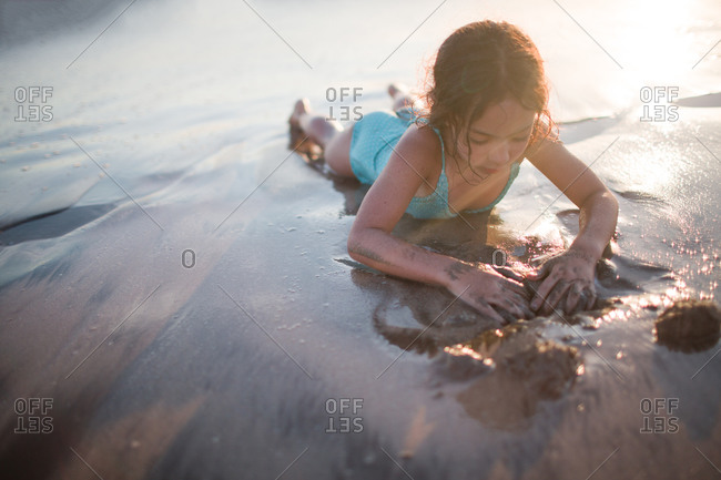 Young girl lying on a muddy beach
