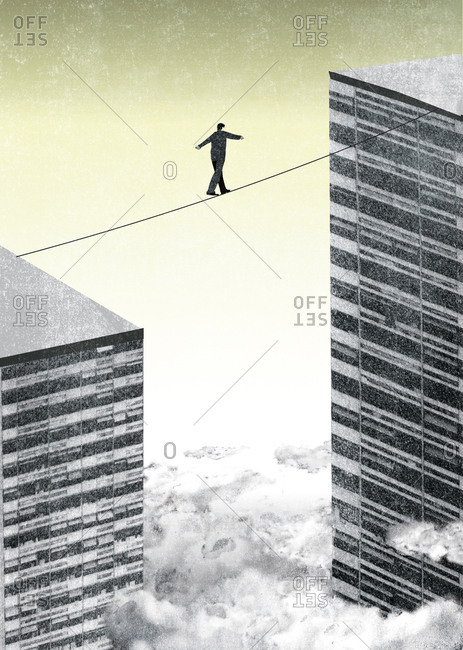 Man tightrope walking between two buildings