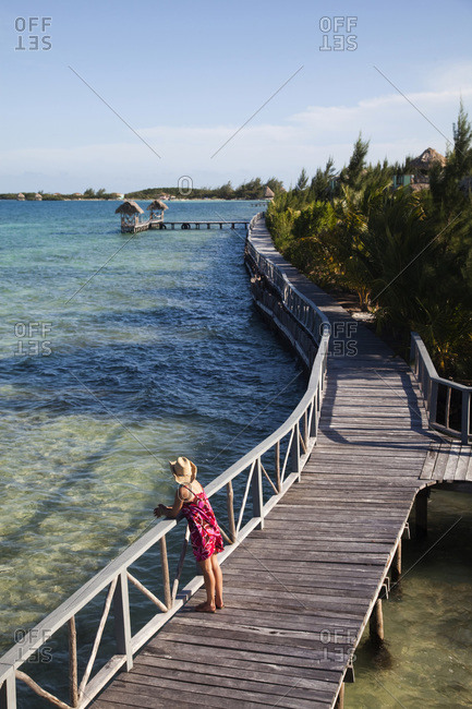 Woman relaxing on a pier in Thatch Caye, Belize