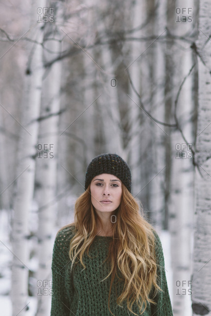 A young woman in a winter hat stands in front a stand of aspens