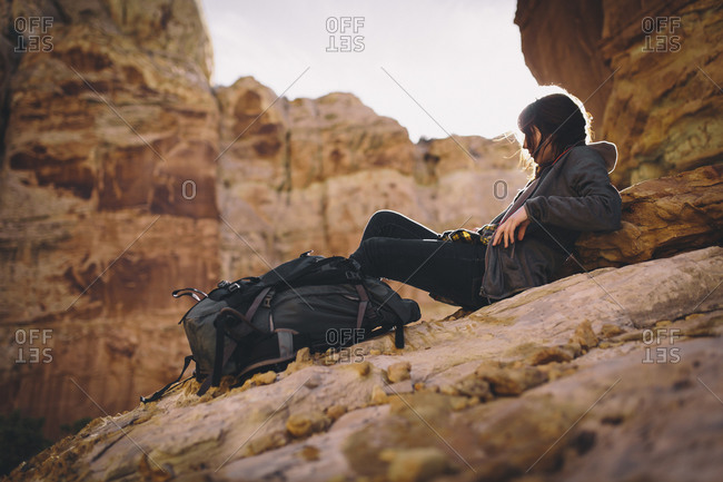 A young woman hiking a slot canyon in southern Utah relaxes at sunset