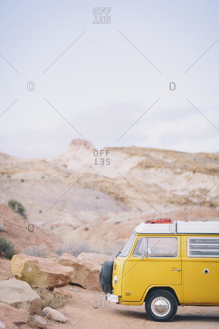 A vintage yellow van is parked at a trailhead in the San Rafael Swell, Utah