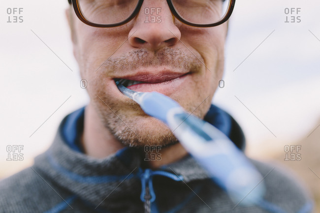 A man smiles with a toothbrush in his mouth while camping