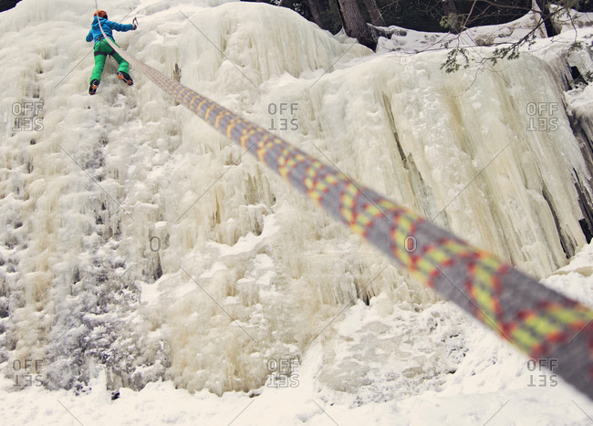 A female ice climber nears the top of an ice cliff