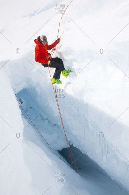 Mountain ranger descending into a crevasse in search for missing climbers on Mount McKinley, Alaska