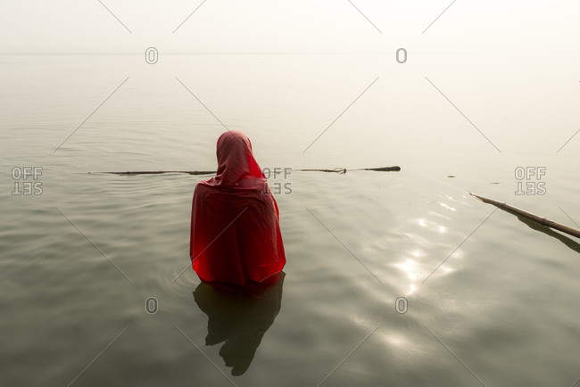 A woman cleanses herself in the waters of the Ganges River in Varanasi, India