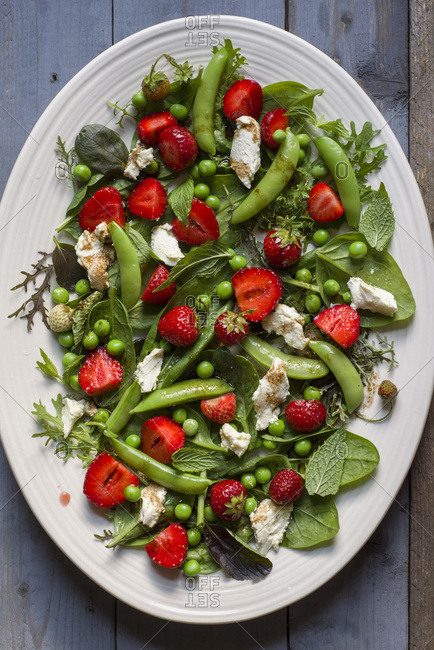 A salad of greens, sugar snap peas, strawberries, mint and goat cheese with a balsamic vinaigrette