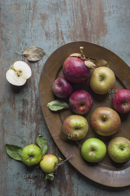 A variety of heirloom and other apple varieties on a copper tray and a rustic wooden board