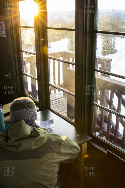 Man looks over a topography map to plan a day of skiing in Montana's backcountry from inside an old fire lookout