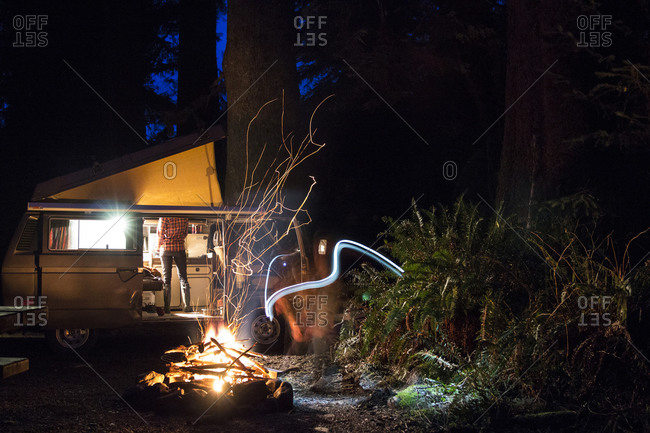 A woman cooks dinner in her Volkswagen bus while her husband tends to the fire on the Olympic Peninsula, WA