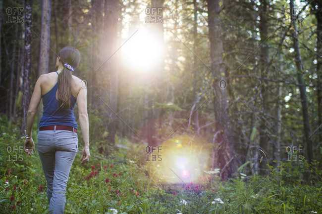 Woman hikes through the forest in Montana's Gallatin National Forest during summer