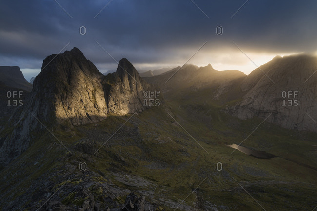 Rays of light illuminate KrŒkhammartind from summit of Markan at sunset