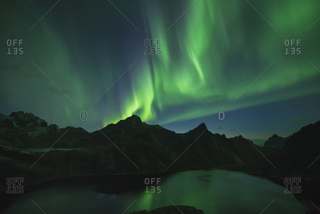 Northern Lights fill sky mountains