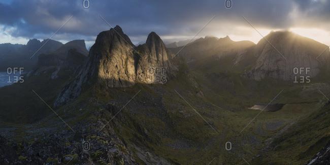 Rays of light illuminate KrŒkhammartind from summit of Markan