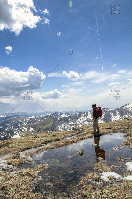 A backpacker stands atop a mountain next to a reflective pond of the blue, cloudy sky in the Indian Peaks Wilderness in Colorado