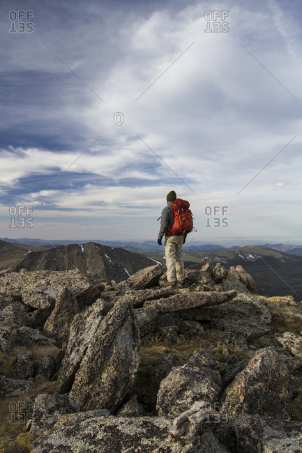 A backpacker stands atop a dramatic landscape in the Indian Lakes Wilderness