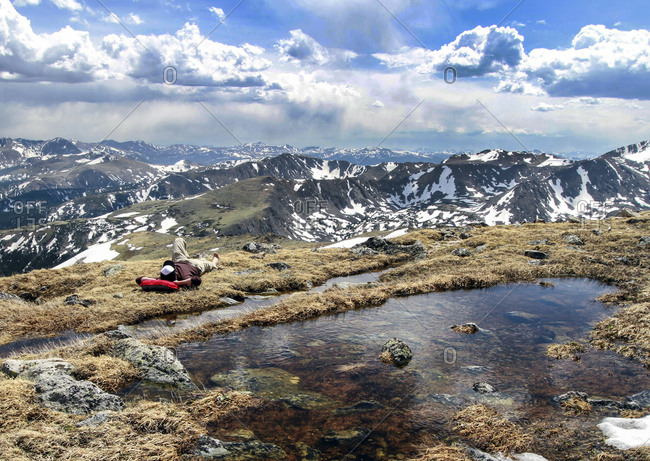 A man lying down and relaxing next to a reflective pond on the grass at the top of the Indian Lakes Wilderness in Colorado