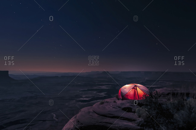 A tent illuminates the starry night on a ridge in Canyonlands National Park