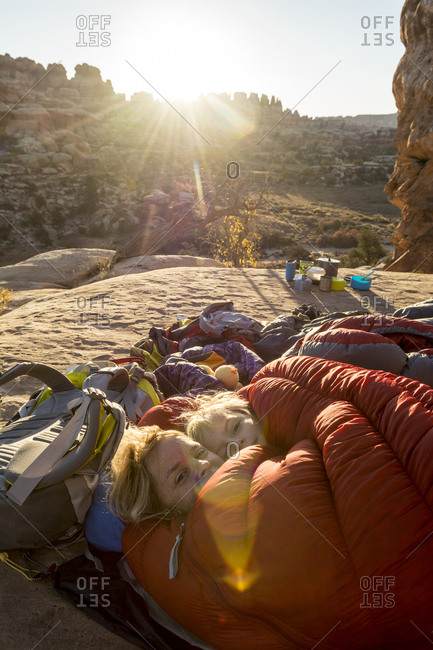A mother and daughter snuggled in sleeping bag at sunrise