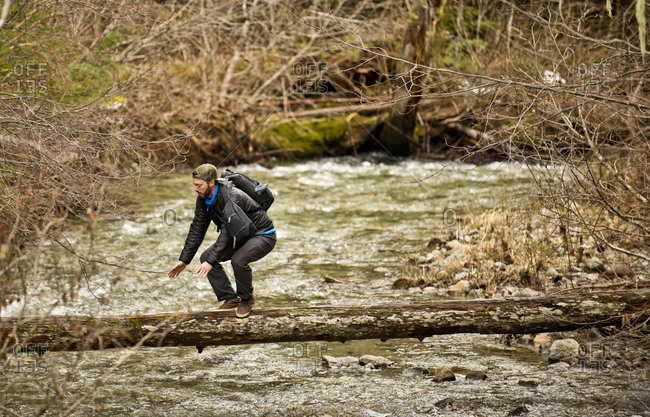 A guy walks across a log overhanging a stream in British Columbia
