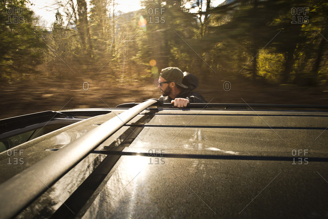 A man rides on the side of a car going down a road in Squamish, British Columbia