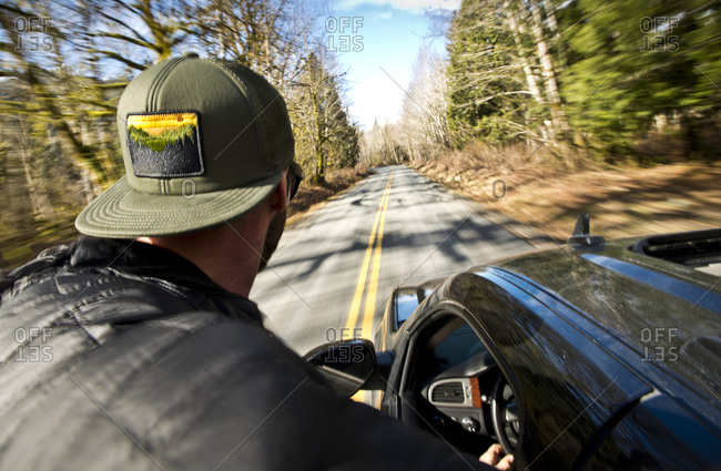 A man riding on the side of a car going down a back road in Squamish, British Columbia