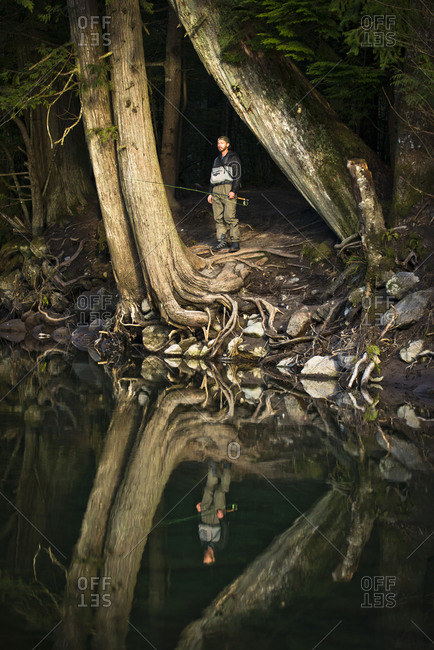 A fly fisherman is reflected in the water as he stands on the side of a river in Squamish, British Columbia