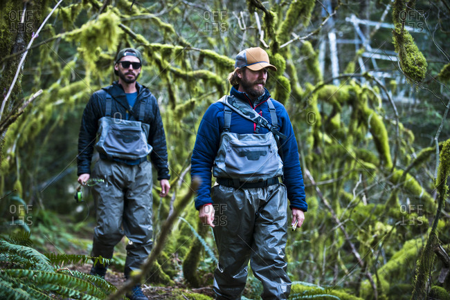 Two fly fisherman walk through a moss covered forest in Squamish, British, Columbia