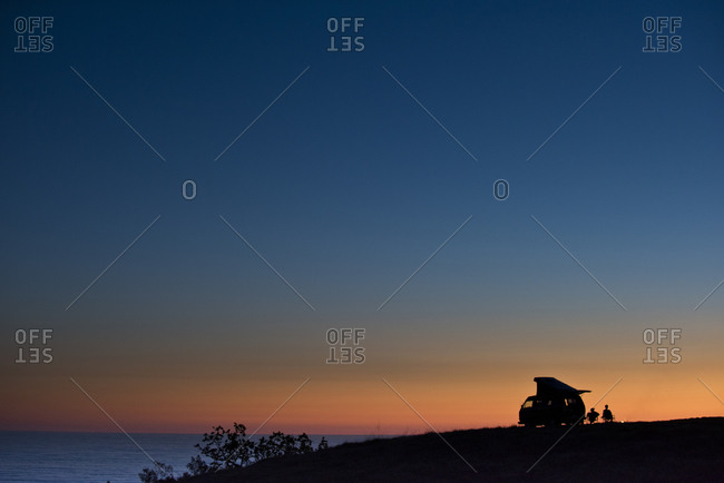 Two friends sit next to their van that sits on a cliff overlooking the ocean at sunset in Big Sur, CA