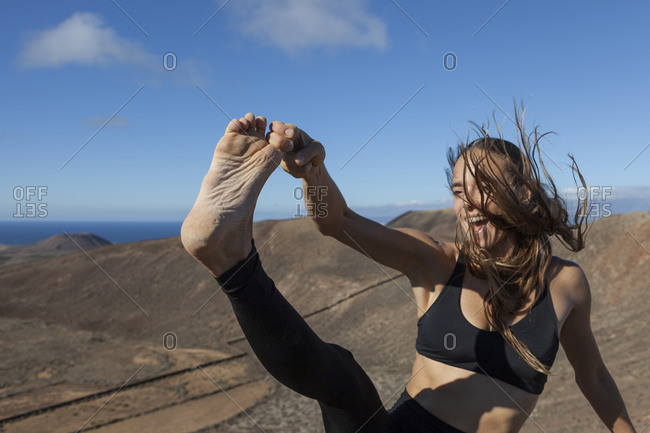 Girl grabbing her toe at the top of a volcano in Fuerteventura, Canary Islands