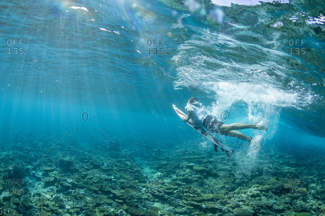 Underwater photo of a surfer duck diving under a wave