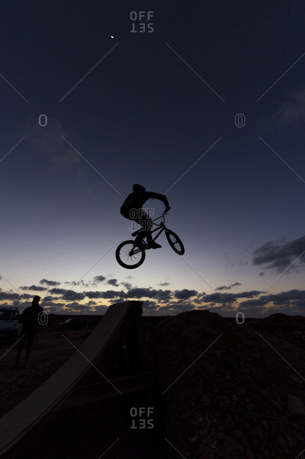 Silhouette of a person with bmx jumping at dusk