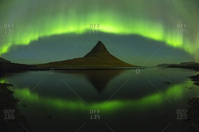 An aurora borealis curtain dances over Kirkjufell mountain in western Iceland