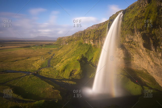 A person admires the waterfall known as Seljalandsfoss in southern Icleand