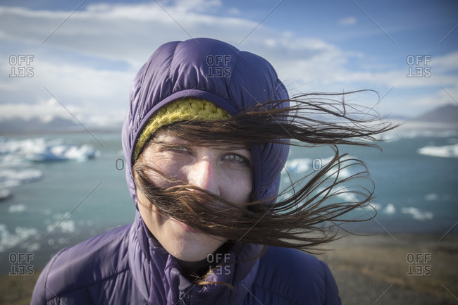 A girl smiles as her hair is blown by the wind at ice lagoon in Iceland