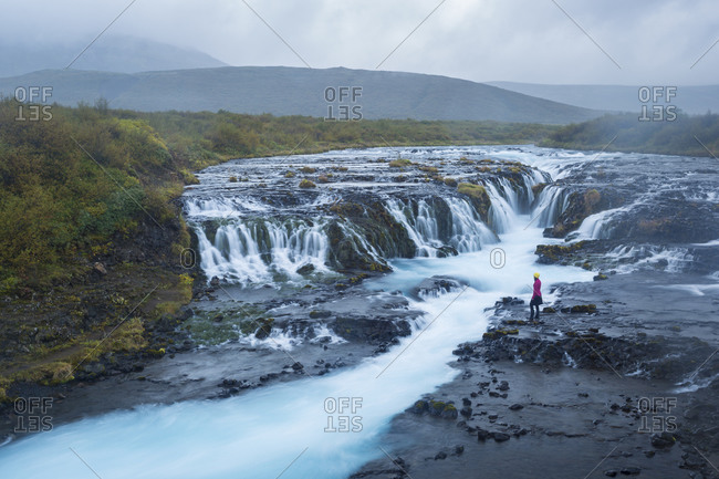 A visitor admires the unique waterfall near the Golden Circle attractions known as Brœarfoss in Iceland