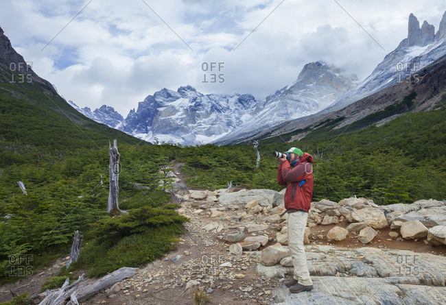A trekker takes a photo in Torres del Paine's French Valley in Chilean Patagonia
