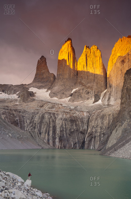 A hiker admires a stormy sunrise on a glacial pool below the iconic Torres